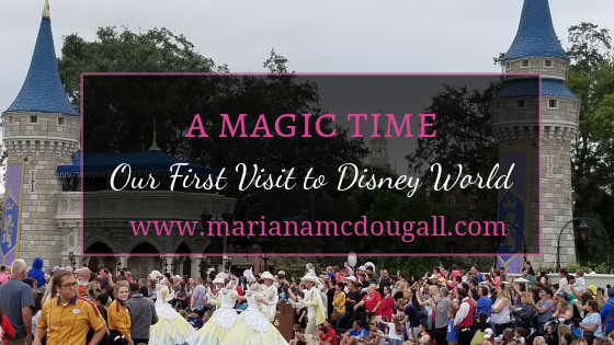 "Blog Title Image. Words in Pink and White on a faint black background and pink border: ""A Magic Time: Our First Visit to Disney World, www.marianamcdougall.com. Picture of Magic Kingdom in the background."