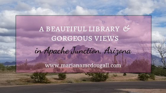 Blog Title Image: black and white letters on faint pink background read: A beautiful library and gorgeous views in Apache Junction, Arizona, www.marianamcdougall.com. Background photo by Mariana Abeid-McDougall shows mountains in the distance.