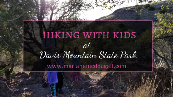 "Title Image: Pink & White lettering say ""Hiking with Kids at Davis Mountain State Park, www.marianamcdougall.com."" Background photo by Mariana Abeid-McDougall. A father, two girls and one boy pose for a photo on the trail at Davis Mountain State Park. They are all holding walking sticks. A tree is to their left, and a mountain is behind them."