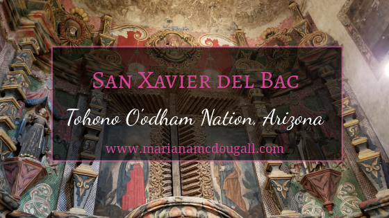"Blog Title image. Pink and white letters read ""San Xavier del Bac, Tohono O'odham Nation, Arizona, www.marianamcdougall.com. A picture of the inside of the church is the background photo. A cross is etched in the wall and surrounded by paintings of saints."