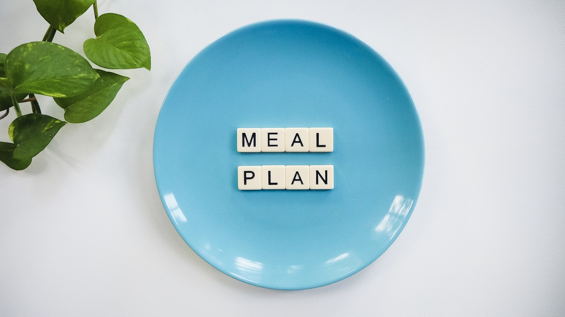 "Word tile spelling out ""MEAL PLAN"" on a blue plate.Photo by Vegan Liftz on Pixabay."