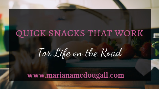 Quick snacks that work for life on the road, www.marianamcdougall.com, pink and white text on faint black background in front of picture of child picking strawberries from kitchen counter Photo by Kelly Sikkema on Unsplash