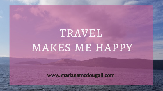 Travel makes me happy, www.marianamcdougall.com, white and black text on faint pink background, in front of a picture of the Newfoundland coast