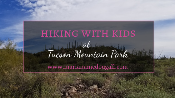 """Blog Title Image. Pink and white letters read """"Hiking with kids at Tucson Mountain Park."""" www.marianamcdougall.com. A picture of a hill covered in desert plants is in the background. Photo by Mariana Abeid-McDougall"""