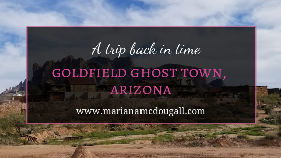 "Blog Post Title Image. White and pink letters read: ""A trip back in time, Goldfield Ghost Town, Arizona, www.marianamcdougall.com. Background photo by Mariana Abeid-McDougall shows some of the wood buildings in the town."