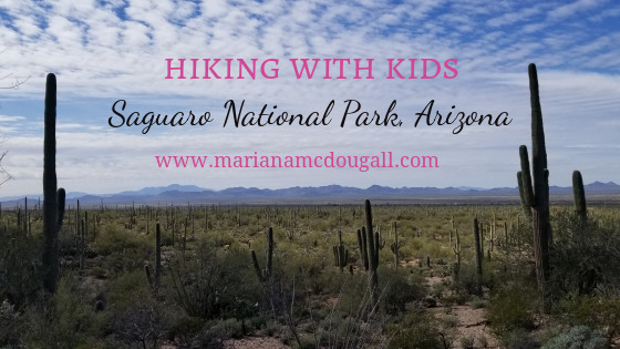"""Blog Post Title image. Pink and black letters read """"Hiking with Kids, Saguaro National Park, Arizona. A picture of the park is in the background and shows several saguaro cactuses."""