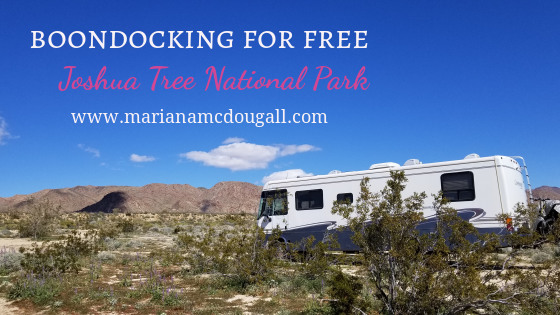 blog title image. White and pink letters read: Boondocking for free Joshua Tree National Park www.marianamcdougall.com. Photo by Mariana Abeid-McDougall shows an RV in the wilderness. Trees and bushes in front of the RV, and mountains in the background.