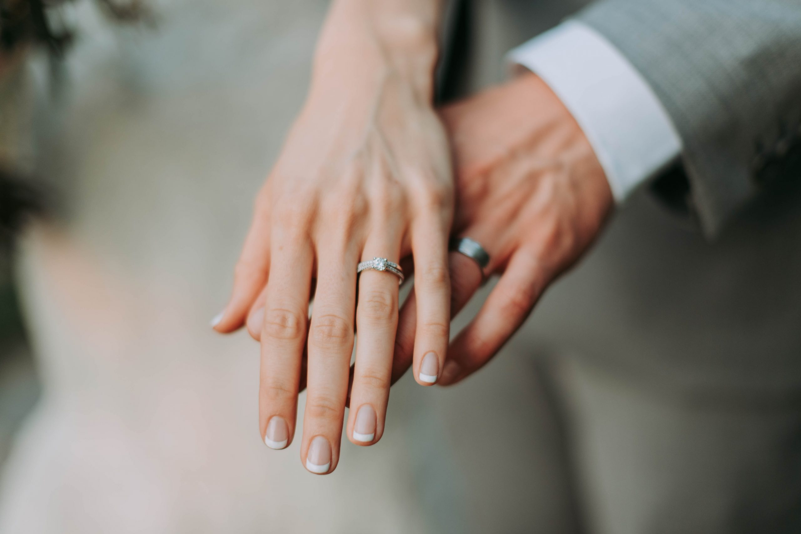 woman and man's hand showing off wedding rings. Photo by Samantha Gades on Unsplash